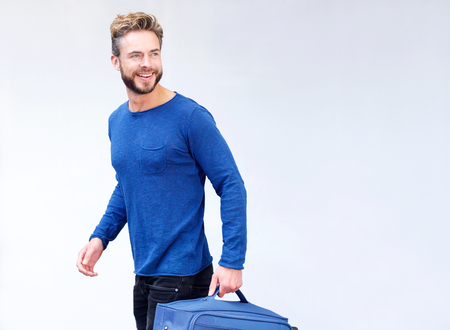 cool guy: Portrait of a cool travel guy with bag smiling against white background