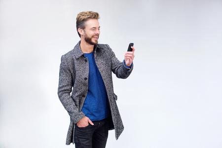 modelos hombres: Retrato de un hombre fresco con barba de pie contra el fondo blanco con el tel�fono m�vil Foto de archivo