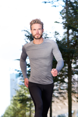 sports clothing: Portrait of an active man running outside