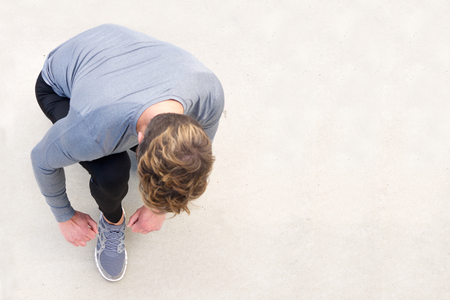 Top portrait sports man tying shoelace before run Stock Photo