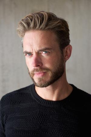 Close-up portret van een coole kerel met een baard kijken naar de camera