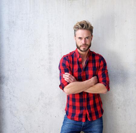 hombre rojo: Retrato de un hombre ocasional hermoso con la barba que presenta con los brazos cruzados