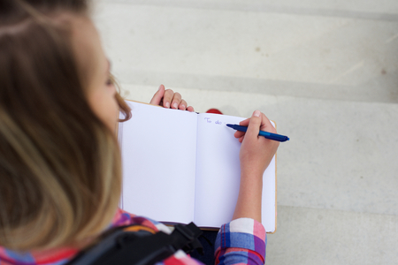 adult writing: Portrait from top of a young woman writing a to do list in book