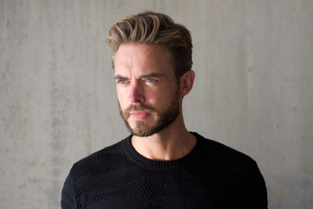 men standing: Close up horizontal portrait of a male fashion model with beard staring Stock Photo