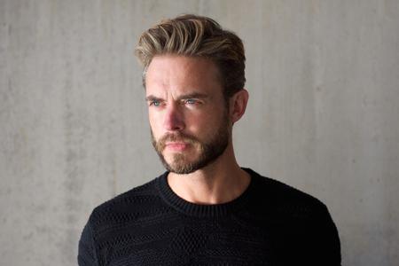 Close up horizontal portrait of a male fashion model with beard staring Foto de archivo