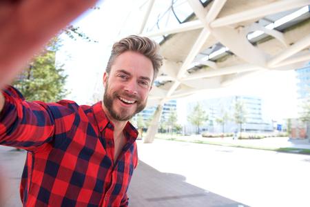 beau mec: Sourire homme prenant selfie en dehors de la ville