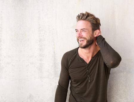 髪で手で笑ってひげとハンサムな男の肖像