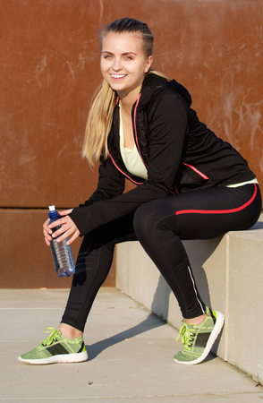 tracksuit: Portrait of a smiling young sports woman sitting outside with bottle of water