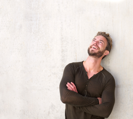 Retrato de un hombre guapo riendo con los brazos cruzados mirando hacia arriba