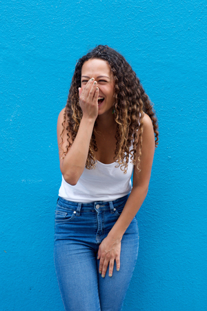 Portrait of young woman laughing standing against a blue wall Stock Photo