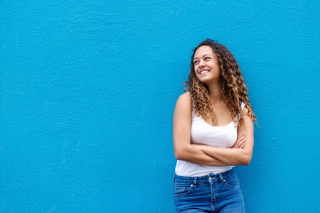 Portrait of relaxed young woman smiling with her arms crossed standing against a blue background Banque d'images