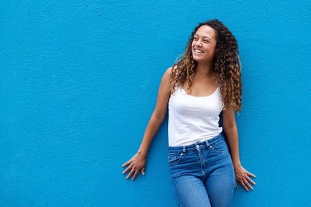 젊은 여자의 초상화 미소 거리 파란색 배경에보고