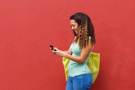 cabello rojo: Retrato de una mujer joven de mensajes de texto en el tel�fono m�vil contra el fondo rojo Foto de archivo