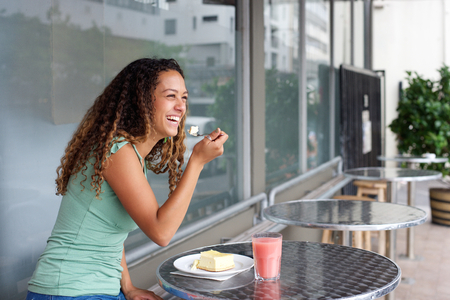 woman eating: Portrait of young woman sitting at cafe eating cake