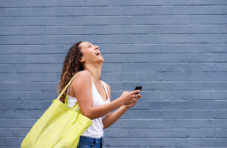 woman on phone: Side portrait of a young woman laughing with mobile phone