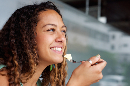 Close up portrait of happy young woman eating cheese cake with fork, looking away smiling.