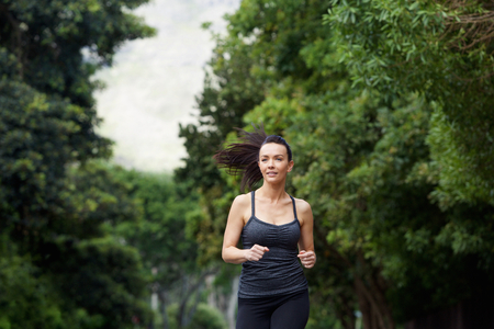 confident woman: Portrait of a running woman exercising outdoors Stock Photo