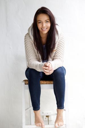 in jeans: Retrato de una mujer joven y sonriente sentado en la silla
