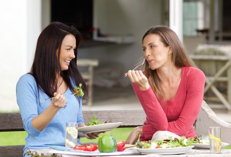 eating salad: Portrait of two female friends enjoying lunch together