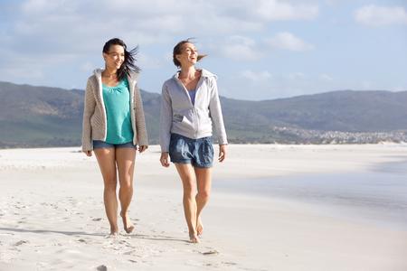 caminando: Retrato de dos mujeres sonrientes amigos caminando juntos en la playa