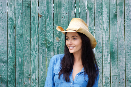 blue shirt: Portrait of an attractive young brunette woman smiling with cowboy hat