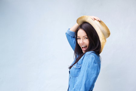 Portrait of a lively young woman laughing with cowboy hat