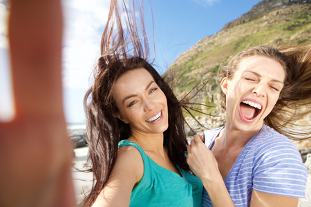 the carefree: Two carefree friends taking selfies outdoors Stock Photo