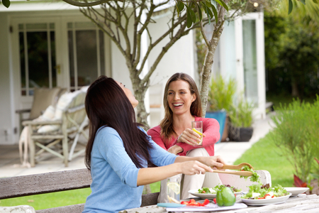 lunch table: Portrait of girlfriends enjoying life at home with lunch Stock Photo