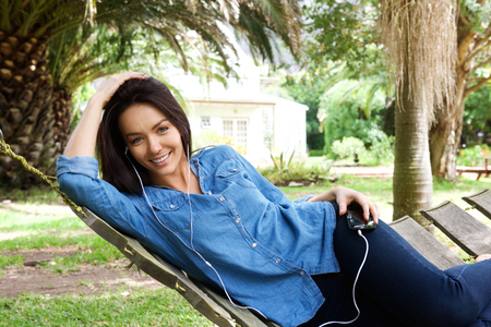 woman relaxing: Portrait of a smiling woman listening to music with earphones Stock Photo