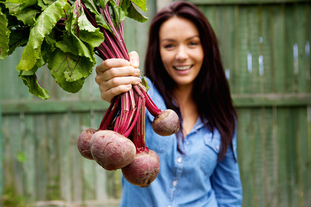 Close up portrait of a smiling woman showing a bunch of beetroots