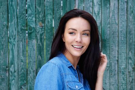 ojos verdes: Cerca de retrato de una mujer sonriente sobre un fondo verde Foto de archivo