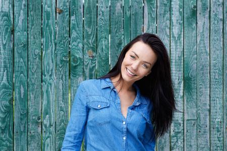 blue shirt: Portrait of a smiling brunette woman with blue shirt