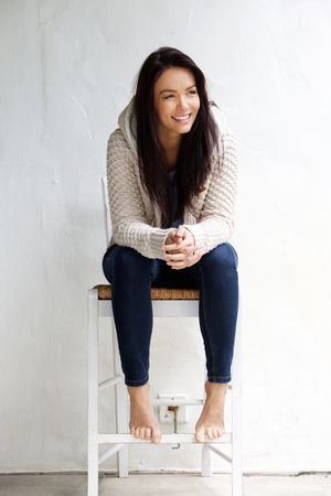 Full length portrait of a smiling young woman sitting on chair Stock Photo