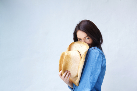 wall covering: Portrait of a smiling woman covering face with cowboy hat Stock Photo