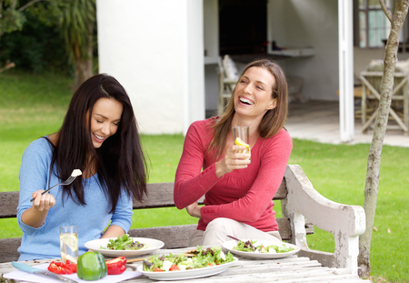 women friends: Portrait of two female friends laughing and having lunch together