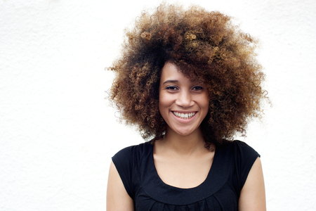Portrait of young african american woman smiling with afro against white background 免版税图像