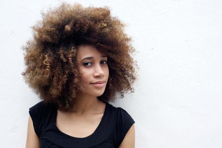 Portrait de la belle femme africaine avec les cheveux bouclés sur le fond blanc