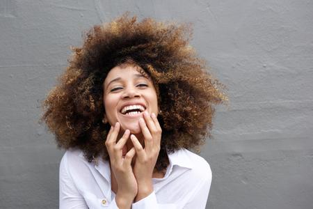 Close up portrait d'une jeune femme en riant avec les cheveux afro