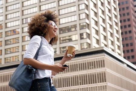 Retrato de la cara de una mujer afroamericana sonriente caminando en la ciudad con el teléfono celular
