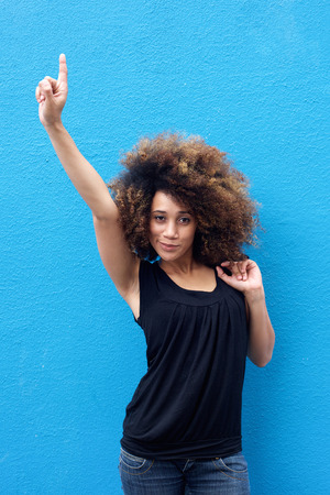 woman pointing: Portrait of young woman pointing finger up Stock Photo