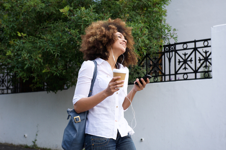 women coffee: Portrait of young woman walking with cell phone and coffee