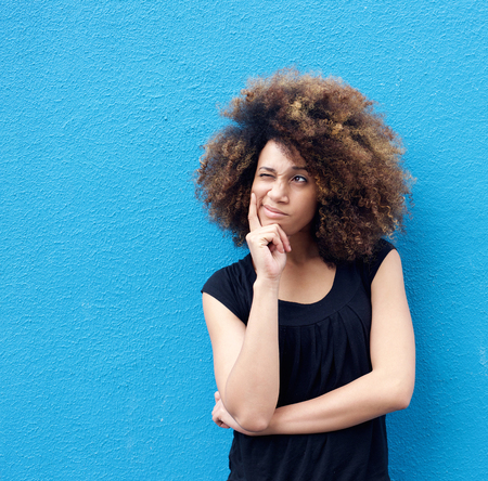 woman think: Portrait of young afro woman thinking against blue background