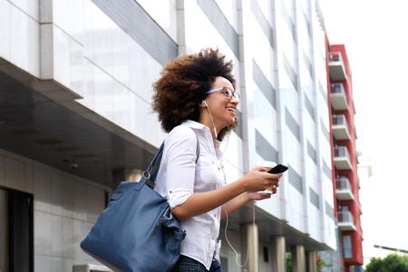 Portrait de marche heureux étudiante dans la ville avec un téléphone mobile