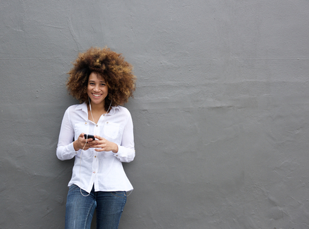 Portrait of young african american woman with afro listening to music on smart phone