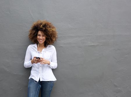 Retrato de joven mujer afroamericana con la escucha a la música afro en el teléfono inteligente