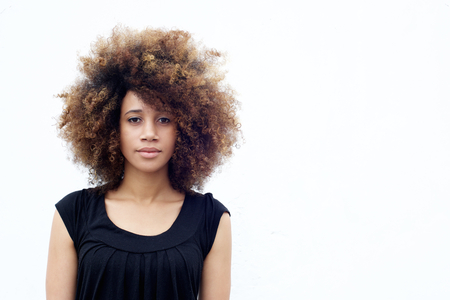 Portrait of young african woman with curly afro hair standing against white background Stock Photo