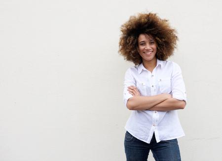 fondo blanco y negro: Retrato de una mujer joven fresca sonriente con los brazos cruzados contra el fondo blanco