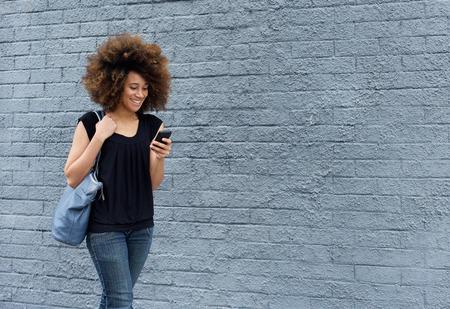 携帯電話と一緒に歩いている笑顔のアフリカの女性の肖像画