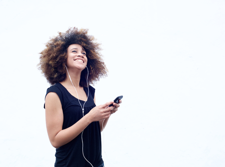 Portrait of young woman smiling with smart phone and mobile phone Archivio Fotografico
