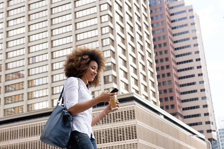 modelos negras: Portrait of young black woman walking and listening to music on city street